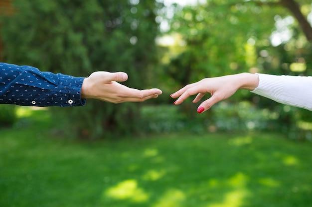 Twee handen raken de verbinding van romantische minnaars