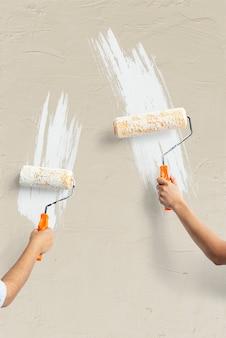 Twee handen schilderen de muur