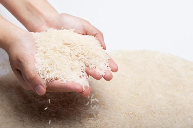 Twee handen van de vrouw die jasmijnrijst, rijst houden die van handen vallen