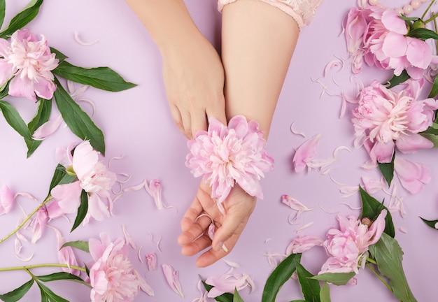 Twee handen van een jong meisje met een gladde huid en een boeket van roze pioenrozen