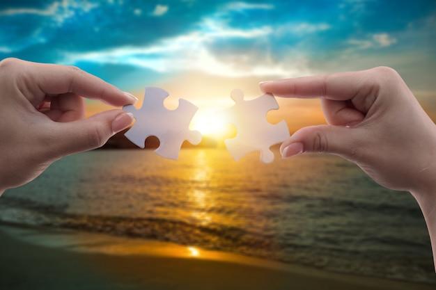 Twee handen verbinden puzzelstukjes tegen de lucht. business concept idee, samenwerking, partnerschap,