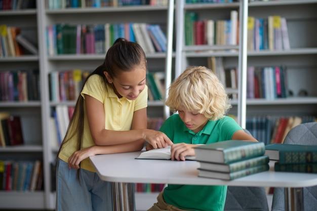 Twee hardwerkende klasgenoten die hun huiswerk maken in de bibliotheek