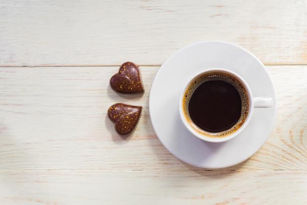 Twee hart vorm chocolaatjes en kopje koffie op houten tafel. valentijnsdag concept. bovenaanzicht