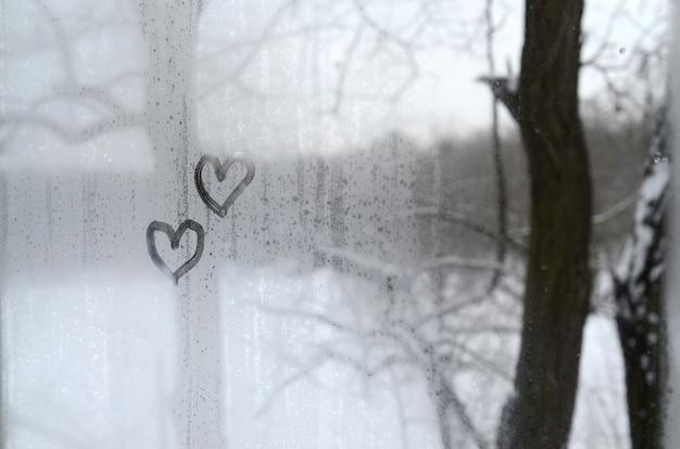 Twee harten die op misted glas in de winter worden geschilderd