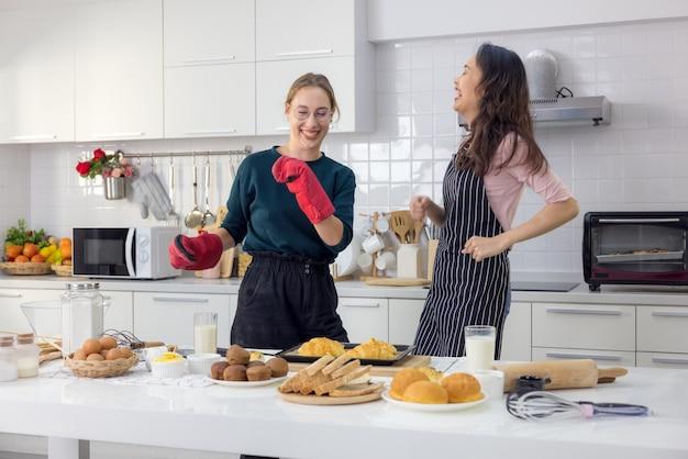 Twee harten die overlopen van liefde. volledige lengte van een mooi jong stel in casual kleding dansen en glimlachen in hun keuken thuis.
