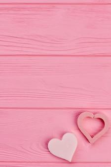 Twee harten en exemplaarruimte bovenop. twee roze harten op roze houten achtergrond, ruimte voor tekst. fijne valentijnsdag.