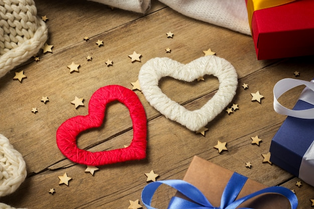 Twee harten, gebreide sjaal, geschenkdozen, lichtgevende slinger op een houten achtergrond.