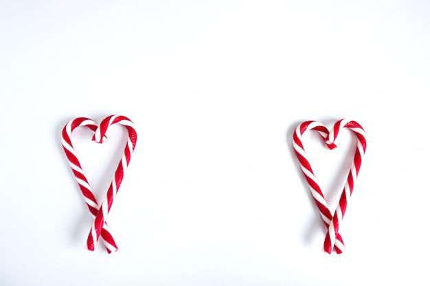 Twee harten gemaakt van kerst snoep. wit en rood snoepriet in de vorm van twee harten op een witte achtergrond