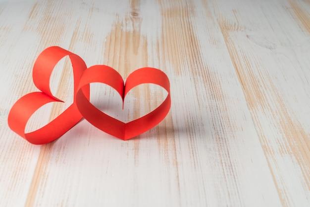 Twee harten gemaakt van lint op houten achtergrond.