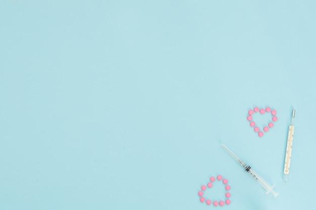 Twee harten gemaakt van roze pillen, thermometer, spuit op lichtblauwe achtergrond