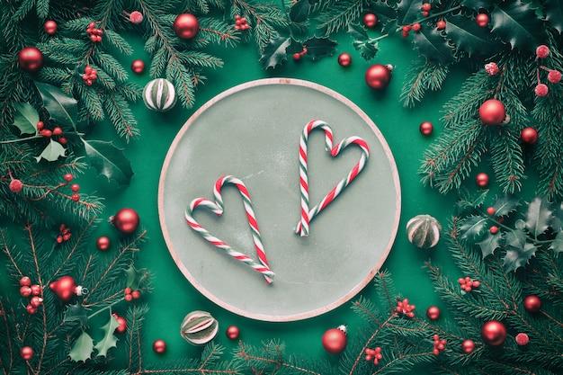 Twee harten gemaakt van snoeprietjes op groene ronde houten dienblad met sparren en hulst takjes, snuisterijen, droge limoen fruit en frosted bessen.