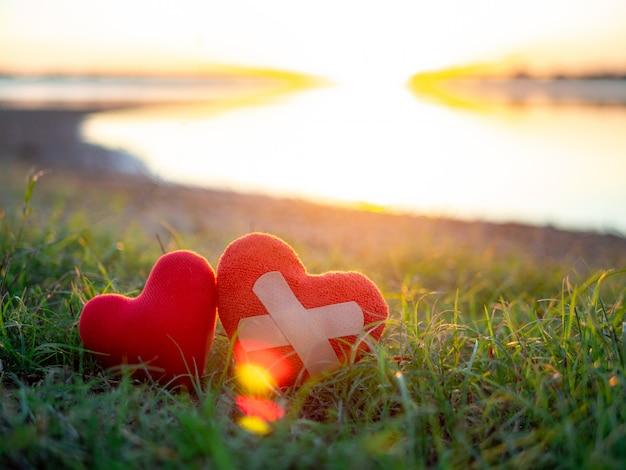 Twee harten naast het meer op de achtergrond van de zonsonderganghemel.