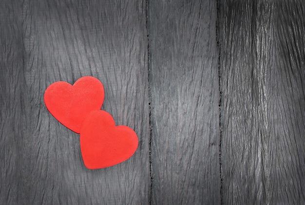 Twee harten op een houten achtergrond. twee rode harten samen op grijze houten achtergrond