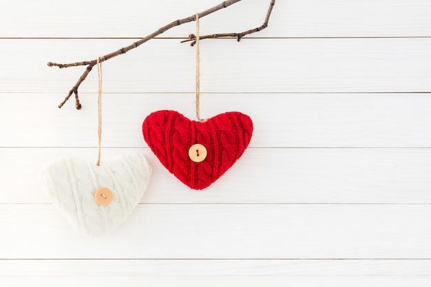 Twee harten op tak op witte houten achtergrond. valentijnsdag concept.