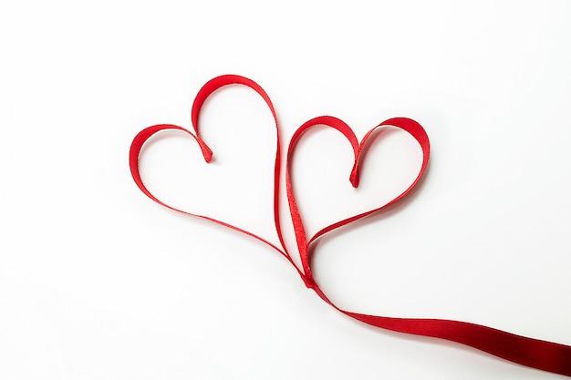 Twee harten samengebonden gemaakt van rood lint