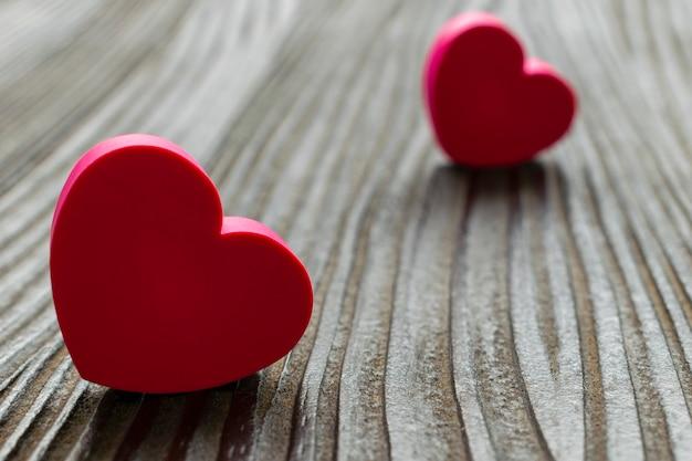 Twee harten uit elkaar op de rustieke houten vloer. valentijnsdag. selectieve aandacht.