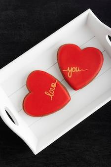 Twee hartkoekjes met inscriptie love you op witte plaat.