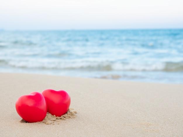 Twee hartvorm gezet op het zand bij het strand en de blauwe overzees vage achtergrond