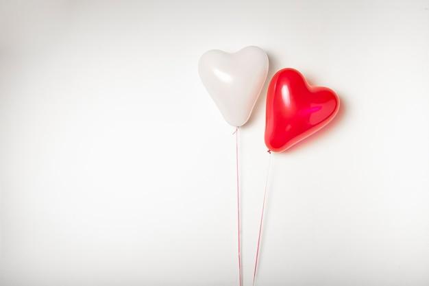 Twee hartvormige ballonnen op een witte achtergrond met ruimte voor tekst