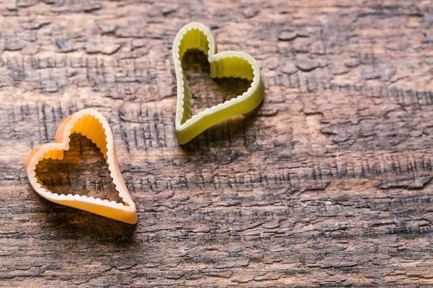 Twee hartvormige italiaanse pasta op houten tafel