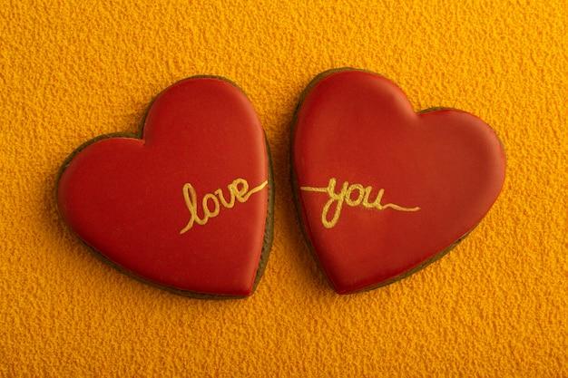 Twee hartvormige koekjes met rode suikerglazuur en inscriptie love you op gele achtergrond.