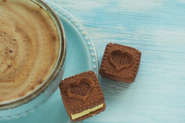 Twee hartvormige koekjes op een schoteltje bij een kopje koffie.