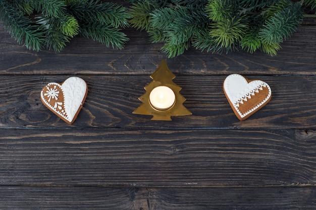 Twee hartvormige peperkoekkoekjes, een kandelaar in de vorm van een kerstboom en pijnboomtakken