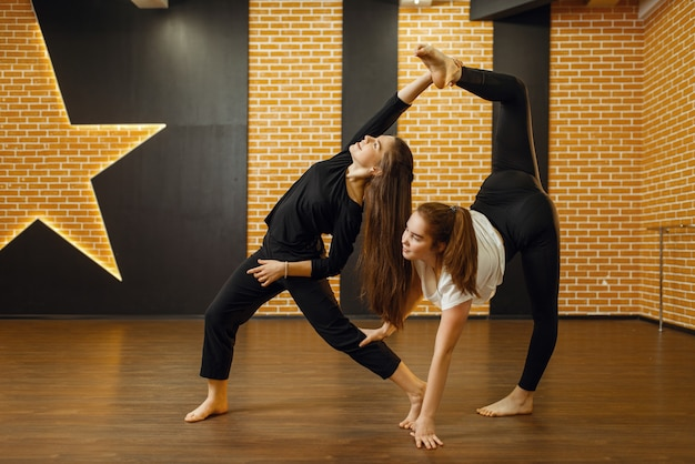 Twee hedendaagse dansartiesten poseert in de studio. vrouwelijke dansers trainen in de klas, moderne gratie dansen, rekoefeningen