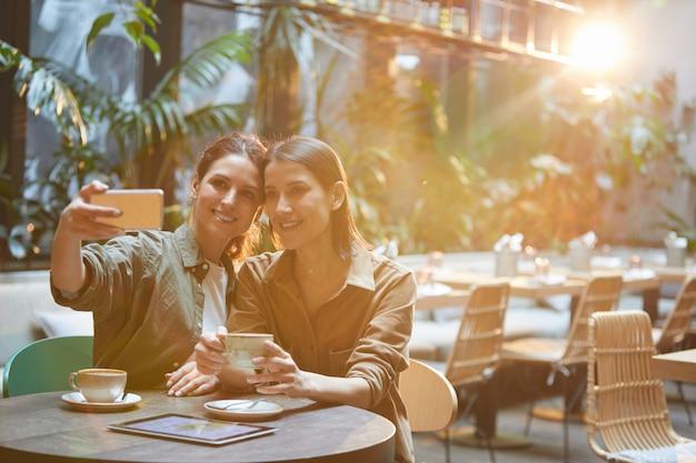 Twee hedendaagse vrouwen selfie foto nemen op cafe tafel