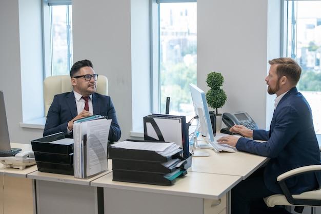 Twee hedendaagse zakenlieden die op hun werkplek met elkaar omgaan