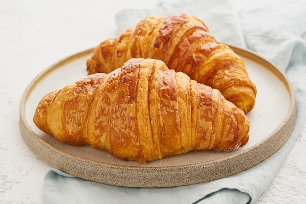 Twee heerlijke croissants op plaat en warme drank in mok. ochtend frans ontbijt met vers gebak