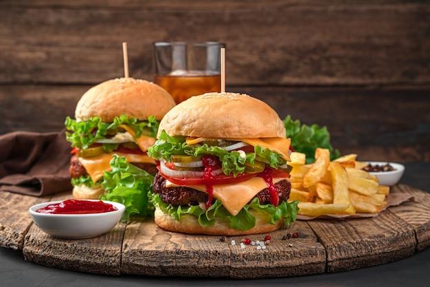 Twee heerlijke hamburgers, franse frietjes, cola en saus op een houten, bruine achtergrond. fast food.