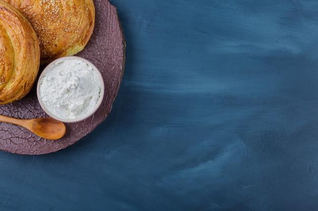 Twee heerlijke traditionele gebakjes en zure room op houten stuk.