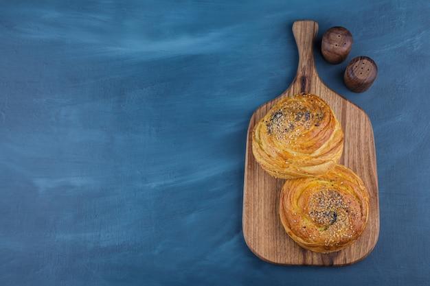Twee heerlijke traditionele gebakjes op houten snijplank.