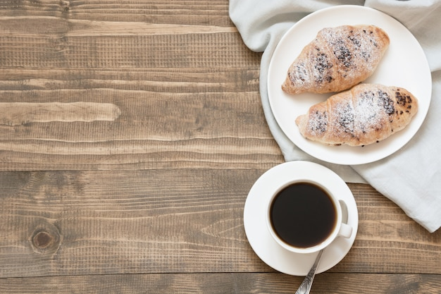 Twee heerlijke vers gebakken chocolade croissants en kopje koffie op een houten bord. bovenaanzicht ontbijt concept.