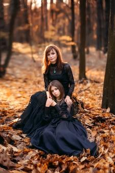 Twee heksen in het herfstbos. moeder en dochter in zwarte jurken