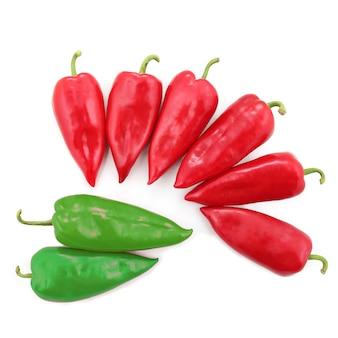 Twee heldergroene en zes rode paprika's op een witte achtergrond. gezond en vitamine eten