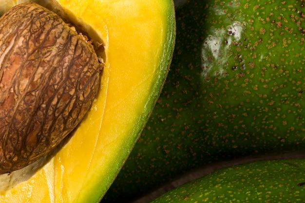 Twee hele avocado's en een avocado in tweeën gesneden op een wit oppervlak.
