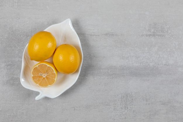 Twee hele en een halve citroen in de plaat op het marmeren oppervlak