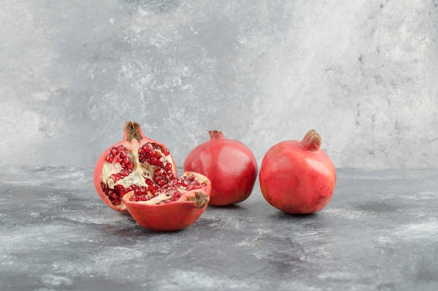 Twee hele granaatappels en gesneden granaatappels op marmeren achtergrond.