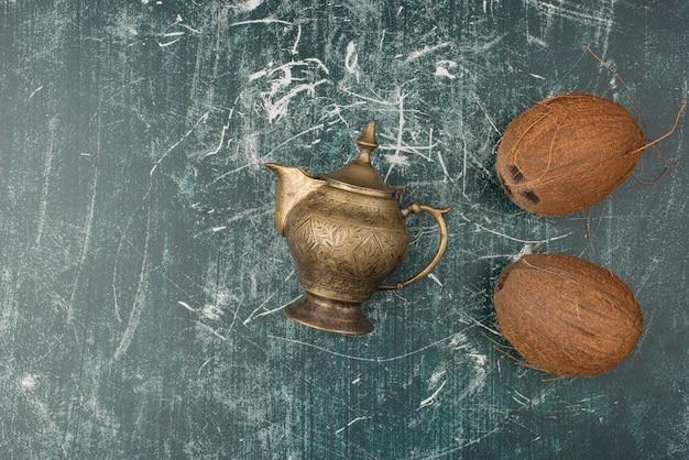 Twee hele kokosnoten en theepot op marmeren oppervlak.