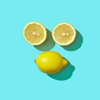 Twee helften en een hele rijpe citroen in de vorm van een gezicht met schaduwreflectie op een blauwe achtergrond