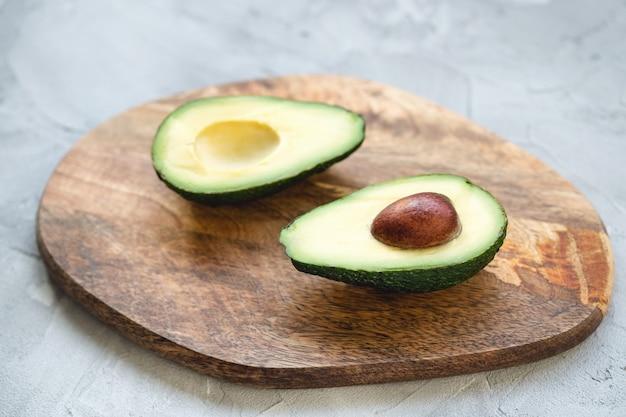 Twee helften van avocado op een houten bord