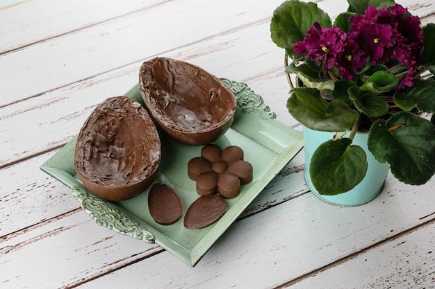 Twee helften van chocoladepaasei, op een klein oud dienblad. naast mini-chocolaatjes en bloemen.