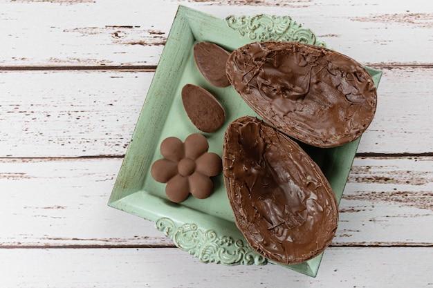 Twee helften van chocoladepaasei, op een klein oud dienblad. naast mini-chocolaatjes.