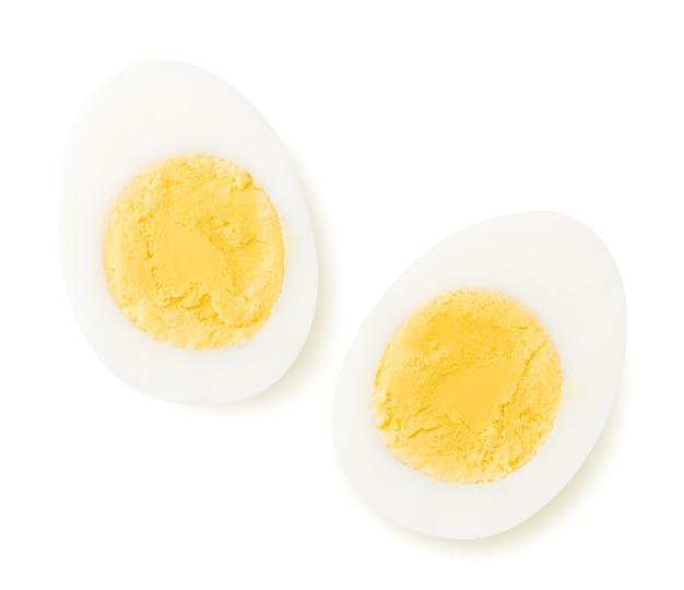 Twee helften van een gekookt ei op een witte achtergrond. het uitzicht vanaf de top