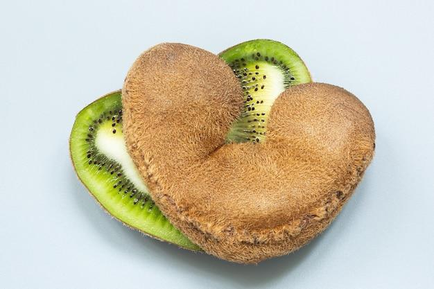 Twee helften van een hartvormige lelijke kiwi in een sectie op een grijze ondergrond.