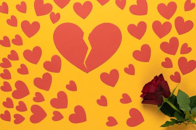 Twee helften van een papieren hart en kleine harten op een felgele achtergrond