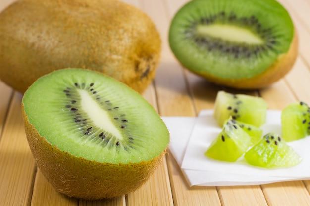 Twee helften van groene kiwi en hele kiwi, kiwi in stukjes gesneden