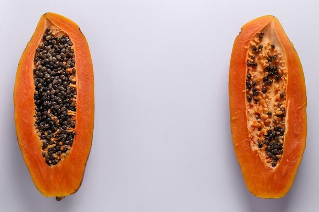 Twee helften van rijpe papaja op wit oppervlak, horizontale oriëntatie, kopie ruimte, bovenaanzicht